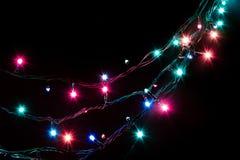 Гирлянда рождества романтичная декоративная освещает рамку на черной предпосылке с космосом экземпляра Стоковое Фото