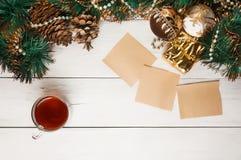 Гирлянда рождества с чашкой чаю и листами стоковые изображения