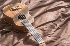 Гитара гавайской гитары на предпосылке кровати стоковое фото rf