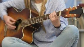 Гитара девушки настраивая, подготовка перед концертом, молодой композитор, урок музыки видеоматериал