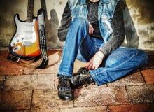 Гитара и человек против стены Стоковое Фото