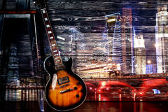 Гитара на предпосылке города ночи Стоковая Фотография