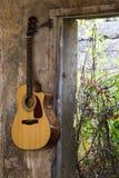 Гитара повиснула на стене в сломленном доме Стоковое Изображение