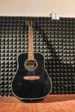 Гитара полагается против стены звукоизоляционной пены Стоковое Изображение