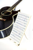 Гитара с написанной музыкой на стойке Стоковые Изображения