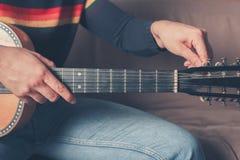 Гитара человека настраивая Стоковые Фото