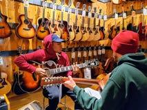 2 гитариста играя в центре гитары стоковое фото rf