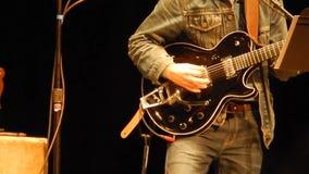 Гитаристы вручают играть черную электрическую гитару - этап горы ` s NPR сток-видео