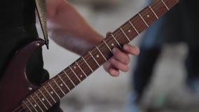 Гитарист играет сольное на электрической гитаре Конец-вверх гитары и рук