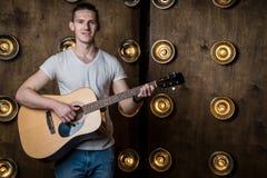 Гитарист, музыка Молодой человек играет акустическую гитару на предпосылке с светами за им Горизонтальная рамка стоковые фото