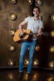 Гитарист, музыка Молодой человек играет акустическую гитару на предпосылке с светами за им Вертикальная рамка стоковые фотографии rf