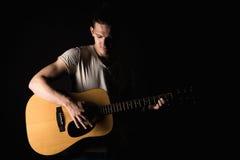 Гитарист, музыка Молодой человек играет акустическую гитару на предпосылке изолированной чернотой Горизонтальная рамка стоковые изображения