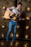 Гитарист, музыка Молодой человек играет акустическую гитару на предпосылке с светами за им Вертикальная рамка стоковая фотография