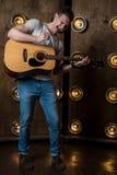 Гитарист, музыка Молодой человек играет акустическую гитару на предпосылке с светами за им Вертикальная рамка стоковые фото