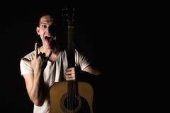 Гитарист, музыка Молодой человек стоит с акустической гитарой и показывает его язык и пальцы на предпосылке изолированной черното стоковые изображения