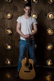 Гитарист, музыка Молодой человек стоит с акустической гитарой на заднем плане с светами за им Вертикальная рамка стоковая фотография