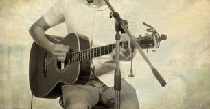 Гитарист на этапе на бумажных фильтрованной предпосылке, нерезкости и grunge текстуры Стоковые Фото