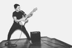 Гитарист утеса музыканта внушительной шальной моды молодой скачет с страстью в студии Стильный скалистый эмоциональный человек че Стоковое фото RF