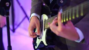 гитарист 4k играет акустическую гитару на этапе ночного клуба, вспышках светов цвета