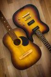 2 гитары акустической и электрической на деревянной предпосылке Стоковое фото RF