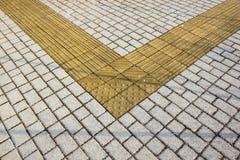Гиды тротуара для шторок Желтые конкретные булыжники на дорожке для людей слепоты стоковая фотография rf