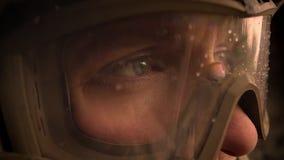 Глаза конца-вверх кавказского военного в шлеме и камуфлирования смотря вперед, падения на стеклах, утихомиривают настойчивое сток-видео