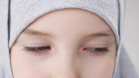 Глаза крупного плана мусульманской предназначенной для подростков девушки в hijab смотря камеру видеоматериал