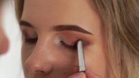 Глаза макияжа с тенями глаза близко вверх Visagiste используя косметическую щетку для теней для век применения на молодой женщине акции видеоматериалы