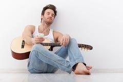 Глаза нот молодого гитариста слушая закрыли Стоковое Фото