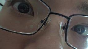 Глаз Брауна раскрывает, деталь зрачок растягивает этничность женщины азиатскую со стеклами 4K акции видеоматериалы