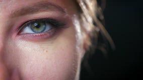Глаз конца-вверх голубой и зеленый с внушительными красочными тенями для век кавказской девушки, смотря холодок камеры, темная пр сток-видео