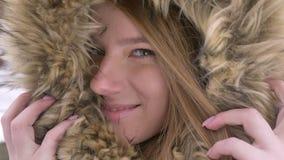 Глаз-портрет конца-вверх красивой молодой кавказской девушки пряча в клобуке меха мило усмехаясь в камеру на улице зимы акции видеоматериалы