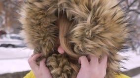 Глаз-портрет конца-вверх красивой молодой кавказской девушки пряча в клобуке меха мило усмехаясь в камеру на улице зимы видеоматериал
