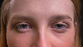 Глаз-портрет конца-вверх официально-одетой женщины спокойно наблюдая в камеру на черной предпосылке акции видеоматериалы