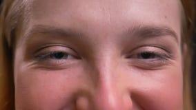 Глаз-портрет конца-вверх официально-одетой женщины smilingly наблюдая в камеру на черной предпосылке видеоматериал