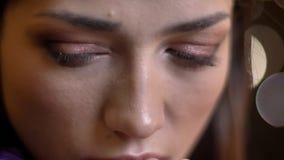 Глаз-портрет конца-вверх очаровывать кавказскую девушку брюнета наблюдая вниз на запачканной предпосылке светов стоковые изображения