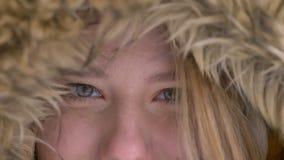 Глаз-портрет конца-вверх привлекательной молодой кавказской девушки в клобуке меха мило усмехаясь в камеру на улице зимы сток-видео