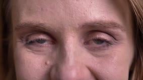 Глаз-портрет молодой белокурой модели наблюдая в камеру с застенчивой и милой улыбкой на черной предпосылке видеоматериал