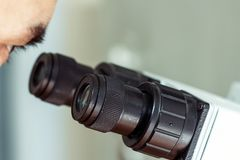 Глаз ` s человека смотрит через микроскоп Черные окуляры конца-вверх оборудования профессиональной лаборатории увеличивая стоковые изображения
