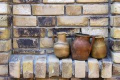 Глиняные горшки на кирпичной стене Стоковое Изображение