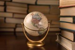 Глобус и много книг на таблица стоковое фото rf