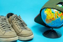 Глобус и старые несенные тапки в сером цвете на голубой предпосылке Географические имена на глобусе на русском стоковое фото
