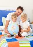 глобус отца смотрящ отпрысков их Стоковое Изображение