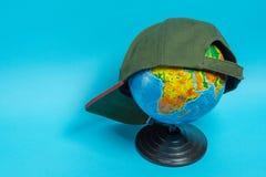 Глобус с зеленой бейсбольной кепкой на ей на голубой предпосылке стоковые изображения rf