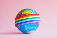 Глобус с лентой радуги LGBT стоковое изображение
