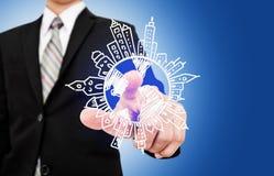 Глобус чертежа бизнесмена с зданиями пальцем на голубой предпосылке Стоковое Фото
