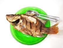 Глубокие зажаренные рыбы на зеленых блюде, ложке и вилке, взгляд сверху, белой предпосылке Стоковая Фотография