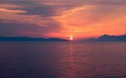 Глубокий покрашенный заход солнца над оттенками моря, сини, золотых и красных Стоковое Изображение RF