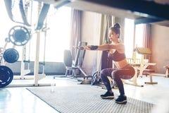 Глубокое сидение на корточках молодой красивой женщины в sportswear делая низкое wh Стоковая Фотография RF