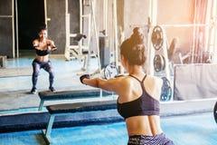 Глубокое сидение на корточках молодой красивой женщины в sportswear делая низкое wh Стоковые Фото